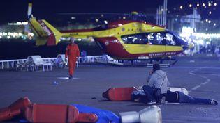 Un hélicoptère de la protection civile est posé près de blessés sur la Promenade des Anglais à Nice (Alpes-Maritimes), le 14 juillet 2016. (ERIC GAILLARD / REUTERS)