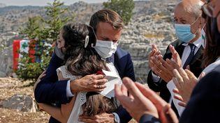 Emmanuel Macron étreint une victime de l'explosionde Beyrouth,lors d'une cérémonie marquant le centenaire du Liban, dans la forêt de la réserve des cèdres de Jaj, au nord-est de Beyrouth, le 1er septembre 2020. (GONZALO FUENTES / POOL / AFP)