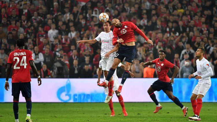 Le Turc du LoscBurak Yilmaz au duel aérien avec le défenseur espagnol de Seville, Sergio Escudero, lors du match Lille-Seville mercredi 20 octobre 2021. (DENIS CHARLET / AFP)