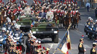 Emmanuel Macron descend les Champs-Elysées avant le début du défilé militaire du 14 juillet 2018. (LUDOVIC MARIN / AFP)