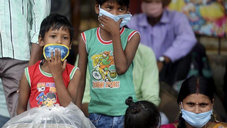 Des enfants se préparent à embarquer dans un train en direction de l'Etat du Bihar, le 18 juin 2020 à Chennai (Inde). (ARUN SANKAR / AFP)