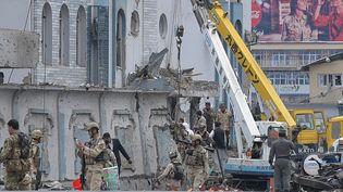Les secours fouillant les décombres du batiments visé parles talibans, à Kaboul, le 19 avril 2016. (SHAH MARAI / AFP)