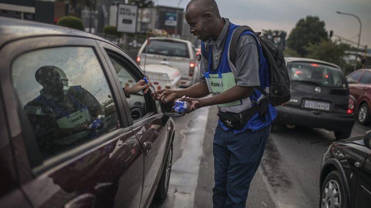 Dans les rues de Johannesburg en Afrique du Sud, le 11 mars 2020, un homme vend des dosettes hydroalcooliques aux passagers des voitures 20 rands (1,10 euro) la dose. (GUILLEM SARTORIO / AFP)