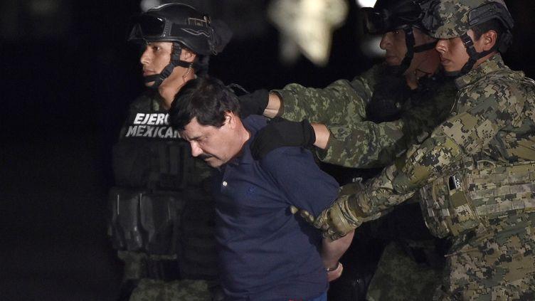 """Le baron de la drogue, Joaquin """"El Chapo"""" Guzman, escorté par des marines mexicains, le 8 janvier 2016 à l'aéroport de Mexico (Mexique). (OMAR TORRES / AFP)"""