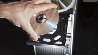 Un CD-ROM posé sur le chariot d'une tour centrale d'un ordinateur de bureau. Photo d'illustration. (GAETAN BALLY / MAXPPP)