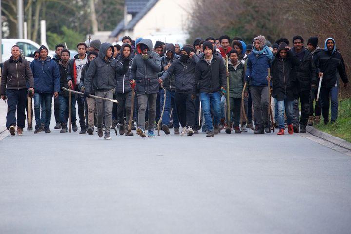 Des migrants, pour certains armés de barre de fer et de bâtons, le 1er février 2018 à Calais (Pas-de-Calais). (MAXPPP)