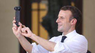 Emmanuel Macron en train de prendre une photo à New Delhi, le 10 mars. (LUDOVIC MARIN / AFP)