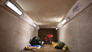 Des volontaires de la Croix rouge discutent avec des sans abri dans un tunnel à la gare deChatou (Yvelines), le 3 novembre 2012. (LOIC VENANCE / AFP)