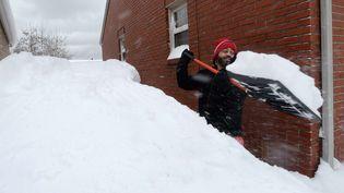 Un habitant d'Erie (Pennsylvanie, Etats-Unis) déneige l'accès à sa maison après des chutes de neige record dans cette ville, le 26 décembre 2017. (GREG WOHLFORD / AP / SIPA)