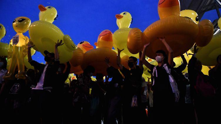 Des manifestants thaïlandais brandissent des bouées gonflables jaunes en forme de canard lors d'une marche à Bangkok en Thaïlande, le 27 novembre 2020. (LILLIAN SUWANRUMPHA / AFP)