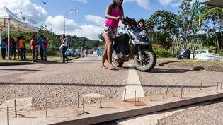 Une Guyanaise pousse son scooter sur une route bloquée par les manifestations, le 29 mars 2017, à Cayenne (Guyane). (JODY AMIET / AFP)