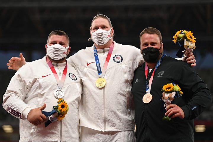 Joe Kovacs, Ryan Crouser et Tomas Walsh (de gauche à droite)sur le podium après la finale du lancer de marteau, le 5 août (INA FASSBENDER / AFP)