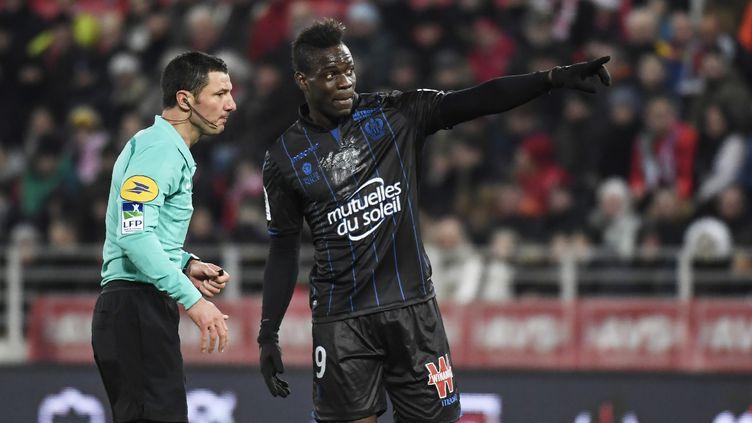 Mario Balotelli se plaint auprès de Nicolas Rainville, l'arbitre du match entre Dijon et Nice, le 10 février 2018 au stade Gaston-Gérard de Dijon (Côte-d'Or). (PHILIPPE DESMAZES / AFP)