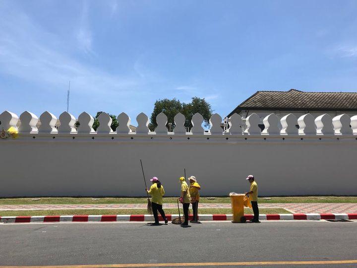 En plein soleil, à midi, par 38 degrés, des femmes équipées de balais sommaires nettoient les abords du palais royal. (THIBAUT CAVAILLÈS / ESP)