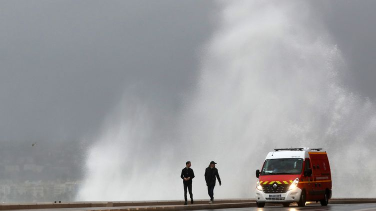 Un véhicule de pompiers circule sur une route battue par les vagues, près de Nice (Alpes-Maritimes), lundi 11 décembre 2017. (VALERY HACHE / AFP)