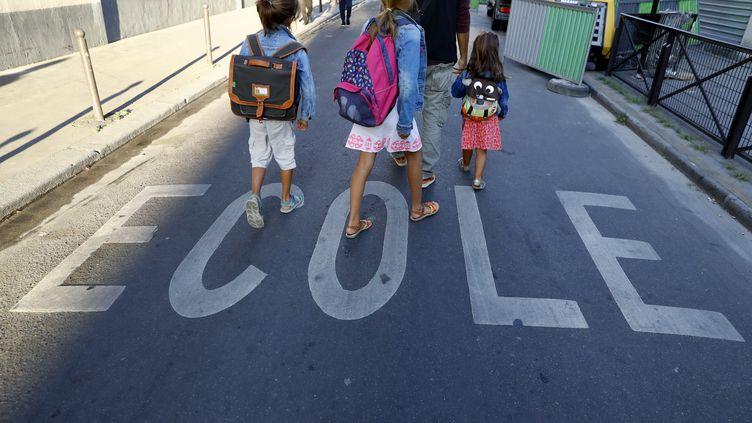Des enfants sur le chemin de l'école, à Paris, le 1er septembre 2016. (PATRICK KOVARIK / AFP)