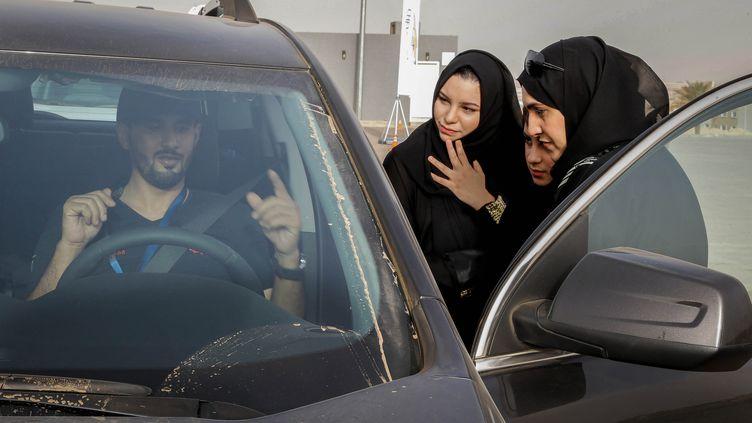 Des femmes saoudiennes découvrent un modèle de voiture lors d'un salon automobile pour les femmes, à Riyad (Arabie saoudite), le 13 mai 2018. (AHMED YOSRI / AFP)