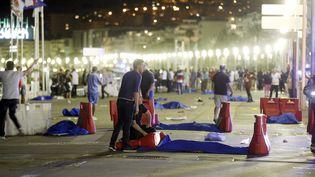 Des corps sont recouverts d'un drap bleu sur la Promenade des Anglais après qu'un camion a foncé dans la foule à la fin du feu d'artifice à Nice (Alpes-Maritimes), le 15 juillet 2016. (NICE MATIN / MAXPPP)
