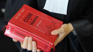 Un avocat tient un code du travail, à Quimper (Finistère). (FRED TANNEAU / AFP)