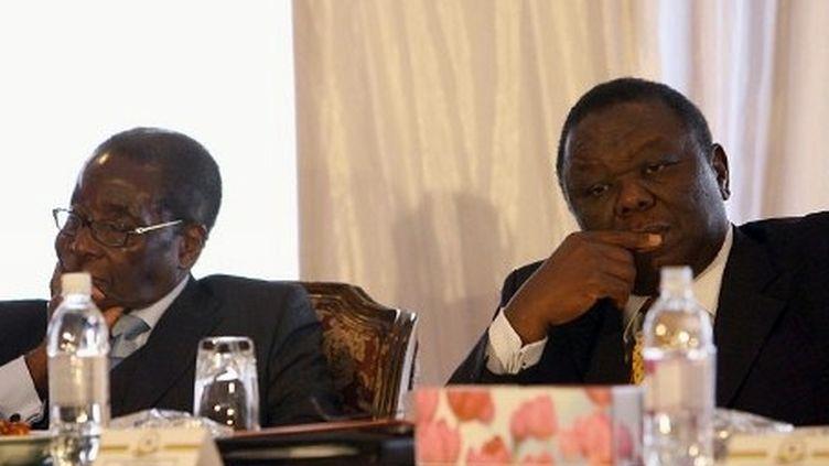 Robert Mugabe et Morgan Tsvangirai, le 24 juillet 2009 à Harare, lors d'une cérémonie de réconciliation... (AFP PHOTO / DESMOND KWANDE)