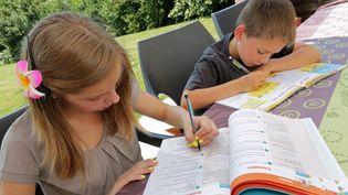 Des enfants s'appliquent à remplirleurs cahiers de vacances, le 15 juillet 2013. (MAXPPP)