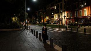 Une femme dans une rue vide à Nice (Alpes-Maritimes), pendant le couvre-feu, le 24 octobre 2020. (VALERY HACHE / AFP)