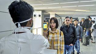Un employé de l'aéroport de Calcutta (Inde) contrôle la température de passagers arrivant de Chine et d'Inde, le 22 janvier 2020. (HANDOUT / MINISTRY OF CIVIL AVIATION / AFP)