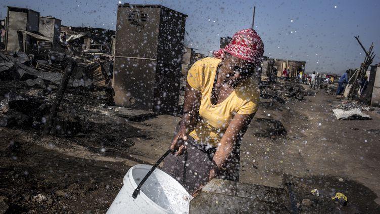 Une femme remplit un seau d'eau dans un bidonville en Afrique du Sud, le 10 octobre 2014. (MARCO LONGARI / AFP)