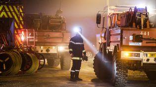 De jour comme de nuit, les soldats du feu maintiennent leur effort pour stopper l'incendie. Un pompier navigue entre les engins à l'aide d'une lampe torche le samedi 25 juillet. A ce moment, le feu progresse toujours, et 350 hectares ont brûlé. (THIBAUD MORITZ / MAXPPP)