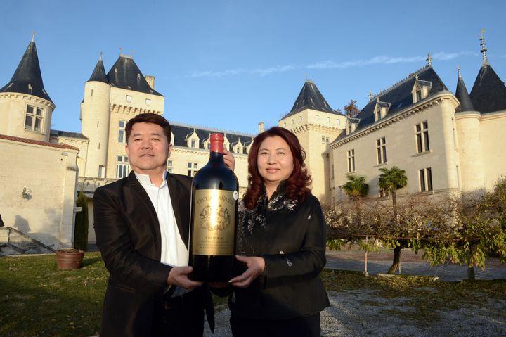 Le millionnaire chinois Lam Kok et son épouse posent devant le Chateau de La Rivière qu'ils viennent d'acquérir, le 19 décembre 2013, en Gironde. (MEHDI FEDOUACH / AFP)