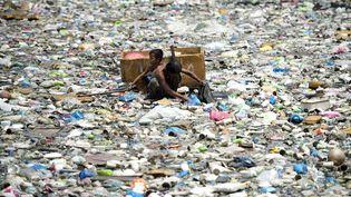Un père et son fils naviguent dans un radeau de fortune pour collecter des bouteilles en plastique sur une rivière polluée à Manille (Philippines), le 19 mars 2015. (NOEL CELIS / AFP)