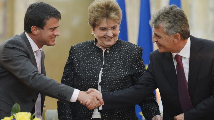Manuel Valls et le ministre roumain de l'Intérieur Mircea Dusa se serrent la main sous le regard de la ministre du travail Mariana Campeanu, le 12 septembre 2012 à Bucarest. (DANIEL MIHAILESCU / AFP)