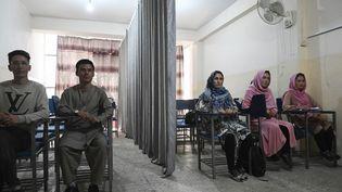 Des étudiants et des étudiantes afghanesséparés par un rideau, le 7 septembre 2021 dans une université privée de Kaboul (Afghanistan). (AAMIR QURESHI / AFP)