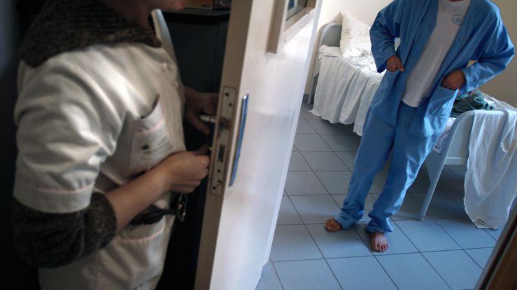 Une infirmière ouvre la porte d'une chambre d'un hôpital psychiatrique où se trouve un patient. (JEAN-PHILIPPE KSIAZEK / AFP)