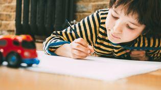 Image d'illustration montrant un enfant en train d'écrire sur une feuille de papier. (BONFANTI DIEGO / CULTURA CREATIVE / AFP)