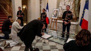 Des personnes signent les registres de condoléances en hommage à Jacques Chirac, à l'Elysée (Paris), le 26 septembre 2019. (GEOFFROY VAN DER HASSELT / AFP)