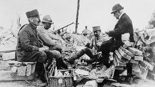 Georges Clemenceau (à droite),le président du Conseil, déjeune sur le front avec des soldats français, dont son fils Michel Clemenceau (au centre, avec le képi), durant la première guerre mondiale.  (STR / AFP)