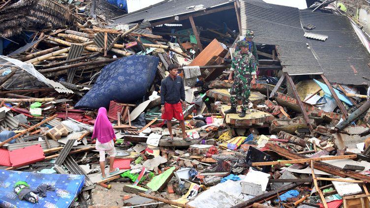 Des personnes observent les dégâts dans le village deSumber Jaya (Indonésie), le 25 décembre 2018, trois jours après le passage dévastateur d'un tsunami lié à une éruption volcanique. (ADEK BERRY / AFP)