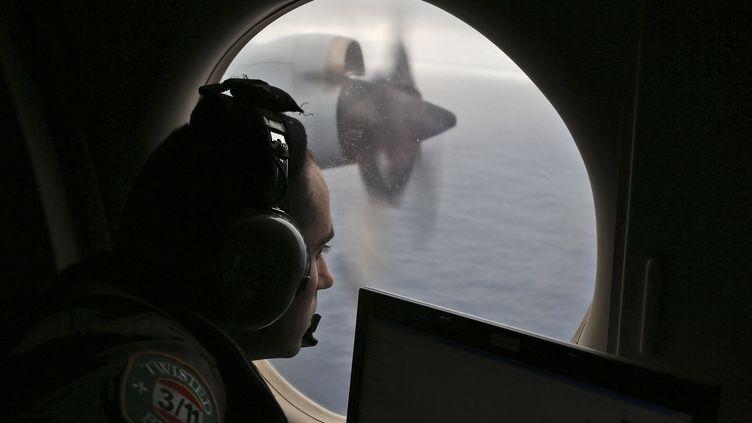 Un officier australien scrute l'océan à la recherche de débris, le 22 mars 2014, dans le sud de l'Océan indien. (ROB GRIFFITH / AFP)