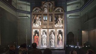 """""""L'Adoration de l'Agneau mystique"""" des frères Van Eyck en partie restaurée est exposée à la cathédrale Saint-Bavon deGand.  (DIRK WAEM / Belga / AFP)"""