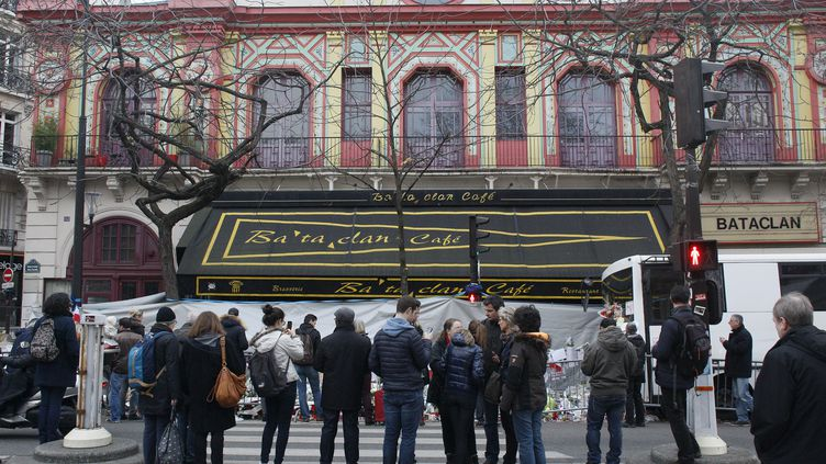 Des passants rendent hommage aux victimes de l'attaque du Bataclan, à Paris, le 13 décembre 2015. (MATTHIEU ALEXANDRE / AFP)