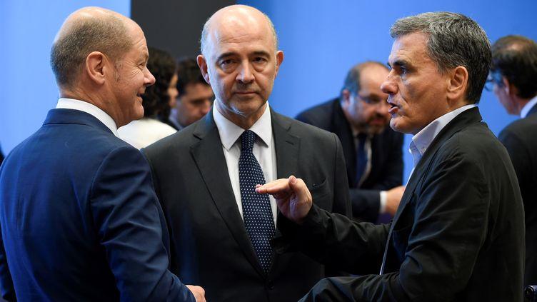 Le ministreallemand aux Finances, Olaf Scholz (g), avecle commissaire européen à l'Economie et aux Finances, Pierre Moscovici, etle ministre grec des Finances, Euclide Tsakalotos (D), lors de la réunion de l'Eurogroupe àSenningen, au Luxembourg le 21 juin 2018. (JOHN THYS / AFP)