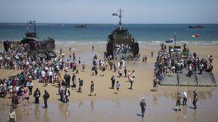 Le public visite des navires de guerre sur la plage d'Arromanches (Normandie), le 6 juin 2014. (JOEL SAGET / AFP)