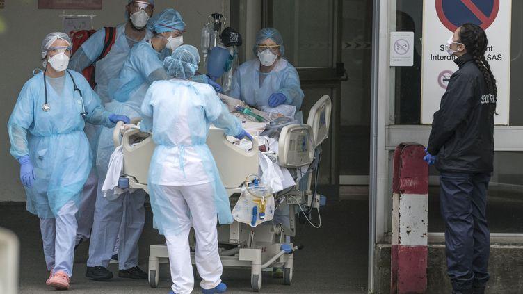 Des soignants transportent un malade du coronavirus, à l'hôpital de Mulhouse (Haut-Rhin), saturé en raison de l'épidémie. (SEBASTIEN BOZON / AFP)