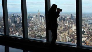 Un homme filme la vue depuis le 102e étage du nouveau World Trade Center, mercredi 20 mai 2015, à New York (Etats-Unis). (TIMOTHY A. CLARY / AFP)