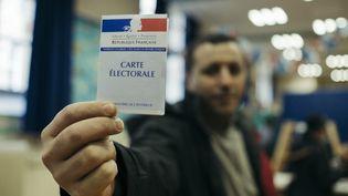Un homme brandit sa carte d'électeur lors du second tour de l'élection présidentielle, dans un bureau de vote du 20e arrondissement de Paris, le 7 mai 2017. (DENIS MEYER / HANS LUCAS / AFP)