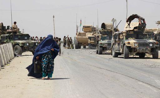 Une femme passe près de véhicules de l'armée afghane dans la province de Kunduz le 24 juin 2015. (Reuters - Stringer)