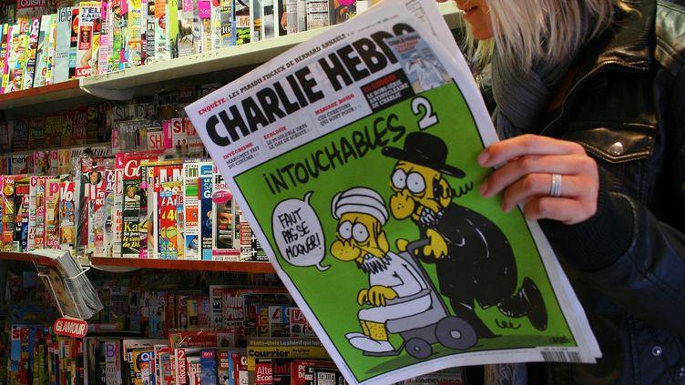 """Une femme lit le numéro polémique de """"Charlie Hebdo"""", sorti mercredi 19 septembre 2012, à Mulhouse (Haut-Rhin). (JEAN-FRAN9OIS FREY / PHOTOPQR / L'ALSACE  / MAXPPP)"""