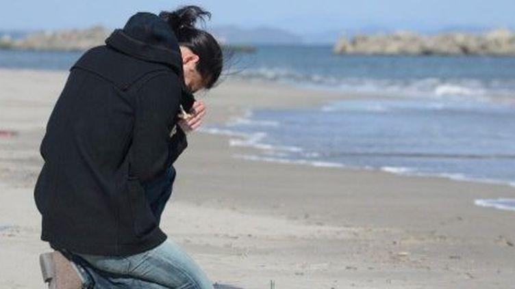 Le 11 mars 2013, à Sendaï, un homme prie, à la mémoire de ses amis disparus lors du tsunami. (Afp/Toru Yamanaka)
