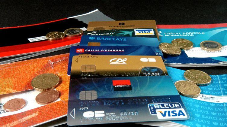 Des cartes bancaires et des carnets de chèques de différentes banques. (FRANCK VALENTIN / MAXPPP)